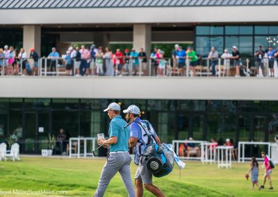 03323 Jordan Spieth & caddy walking in front of clubhouse on 18th hole, Trinity Forest Golf Club